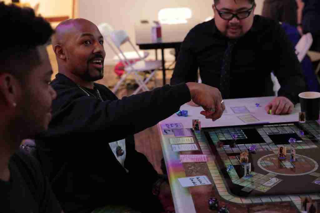 Miles explains his next action and prepares for a roll in Project Violacea. In front of him, you can see the four cards that represent his character's abilities, public face, and equipment. Card and rule designs were made in collaboration with Wrong Brothers Gaming.